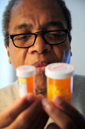 Black man taking pills for high blood pressure.