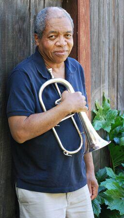 flugelhorn: Jazz musician posing with his flugelhorn outside.