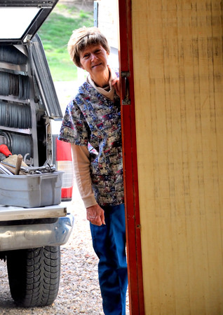 rancher: Female rancher watching her farrier work on her horse.