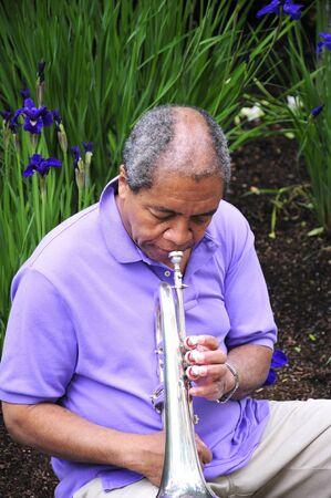flugelhorn: African american male blowing his flugelhorn outdoors.