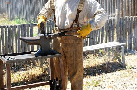 farrier: Farrier working on a horseshoe outside. Stock Photo
