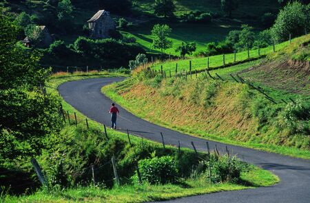 cantal: walker on a small winding road of Cantal, France