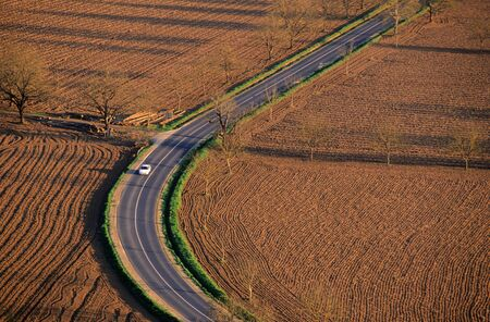 macadam: aerial view of a road crossing cultivated land in the Dordogne, France.