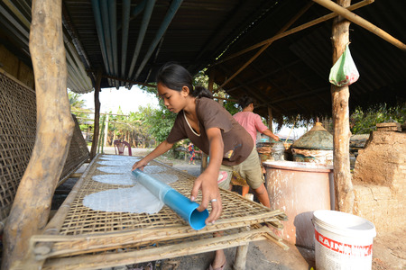 coking: Don Khong, Laos  Unidentified woman making rice paste on March 15, 2014 in Don Khong, Laos