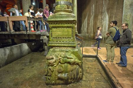 cisterna: Istanbul, Turkey - May 14, 2016: Unidentified people at the head of Medusa in the Cistern Basilica on May 14, 2016 in Istanbul, Turkey.