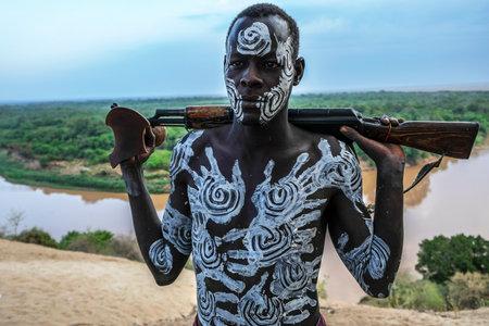 Omo Valley, Ethiopië - 26 januari: Unidentified Karo man poseert met vuurwapen in zijn hand op 26 januari 2018 in Ethiopië. De mensen in de Omo-vallei zouden kunnen verdwijnen door een waterkrachtcentrale.