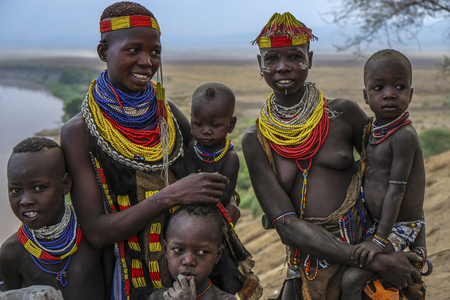 Omo Valley, Ethiopia - January 26: Unidentified Karo women and their children with Omo River in the background on January 26, 2018 in Omo Valley, Ethiopia. Editorial