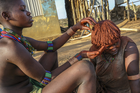 Turmi, Ethiopia - January 25: Unidentified woman combing another woman. Hamer woman usually comb their hairs with soil on January 25, 2018 in Turmi, Amo valley, Ethiopia.