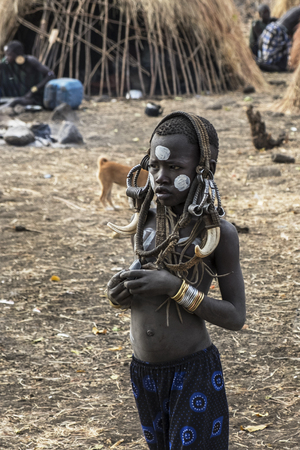 Omorate Ethiopia - January 24: Unidentified child from Mursi tribe posing for a portrait in his village with the traditional houses of the Mursi in the background on January 24, 2018 in Ethiopia. Editorial