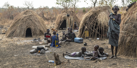 Omorate, Ethiopia - January 24: Unidentified women and children of the Mursi tribe resting in their village surrounded by the traditional houses of the Mursi on January 24, 2018 in Ethiopia.