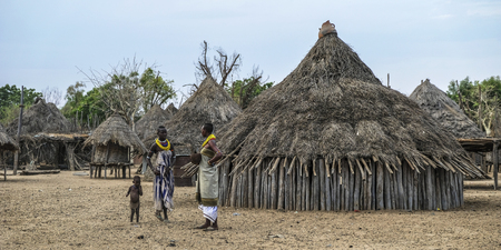 Omo Valley, Ethiopia - January 26: Two unidentified women of the Karo tribe speaking in their village with the typical houses of the Karo in the background on January 26, 2018 in Omo valley, Ethiopia.