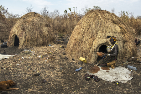 Omorate Ethiopia - January 24: Unidentified woman of the Mursi tribe drinking in a bowl next to her house in a traditional village of the Mursi on January 24, 2018 in Omo valley, Ethiopia.