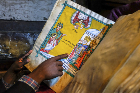 Tigray, Ethiopia - January 11: A young monk reading an ancient bible in the Abuna Aregawi church, the oldest in Ethiopia, in the Debre Damo monastery on January 11, 2018 in Tigray region, Ethiopia. Editorial