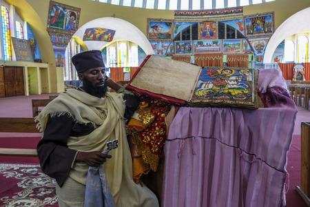 Aksum, Ethiopia - January 12: Unidentified man demonstrates ancient Bible in Amharic language in the church of Our Lady Mary of Zion on January 12, 2018 in Aksum, Ethiopia.
