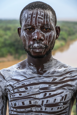 Omo Valley, Ethiopia - January 26: Unidentified Karo Man with Omo River in the background on January 26, 2018 in Omo Valley, Ethiopia. Karo tribes are famous for their body painting.