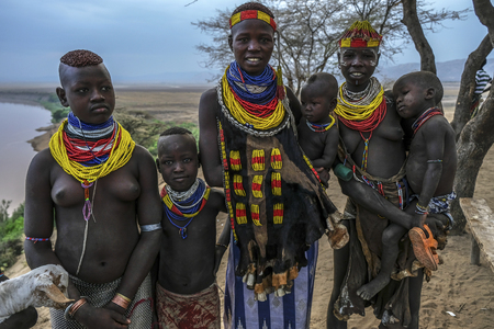Omo Valley, Ethiopia - January 26: Unidentified Karo women and their children with a goat with Omo River in the background on January 26, 2018 in Omo Valley, Ethiopia.