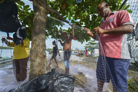 Cartagena, Colombia - August 4: Fishermen fixing the fishing nets on the beach of Cartagena on August 4, 2017 in Cartagena, Colombia.