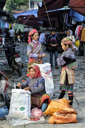 Bac Ha, Vietnam - August 26: Women seller of the Hmong indigenous tribe in the local market on August 26, 2018 in Bac Ha, Vietnam.