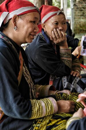 Ta Phin, Vietnam - August 24: Red Dao women sewing in the village on August 24, 2018 in Ta Phin. Red Dao people are Chinese minority in Vietnam. Éditoriale
