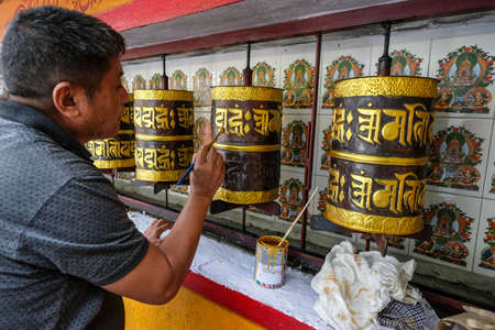 Gangtok, India - October 2020: A man painting the prayer wheels of the stupa in the stupa in the Sera Jey Drophenling Monastery in Gangtok on October 23, 2020 in Gangtok, Sikkim, India. Stock Photo - 158370469