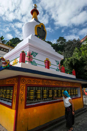 Gangtok, India - October 2020: A woman turning the prayer wheels of the stupa in the Sera Jey Drophenling Monastery in Gangtok on October 23, 2020 in Gangtok, Sikkim, India. Editorial