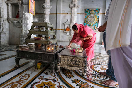Tezpur, India - November 2020: A woman making an offering in the Shree Jain Swetamber Gauri Parswanath Temple in Tezpur on November 14, 2020 in Assam, India.