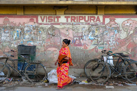 Agartala, India - December 2020: A woman passing by a wall with a sign inviting you to visit Tripura on December 19, 2020 in Agartala, Tripura, India.
