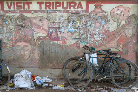 Agartala, India - December 2020: Bicycles leaning against a wall with a sign that invites you to visit Tripura on December 19, 2020 in Agartala, Tripura, India.