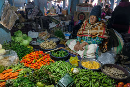 Moirang, India - December 2020: A woman selling vegetables in the Moirang market on December 29, 2020 in Manipur, India.