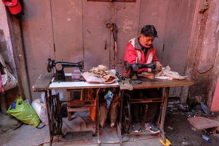 Imphal, India - December 2020: Tailor working with a sewing machine on the street on December 30, 2020 in Imphal, Manipur, India.