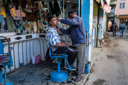 Imphal, India - December 2020: A barber with a mask in his barbershop shaving a client on December 30, 2020 in Imphal, Manipur, India.