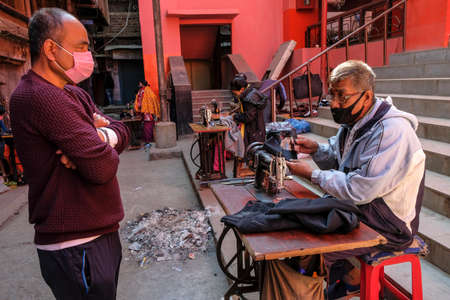 Imphal, India - December 2020: Tailors working with a sewing machine on the street on December 30, 2020 in Imphal, Manipur, India.