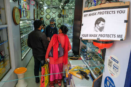 Imphal, India - December 2020: People with masks shopping at a watch shop on December 30, 2020 in Imphal, Manipur, India. Editorial