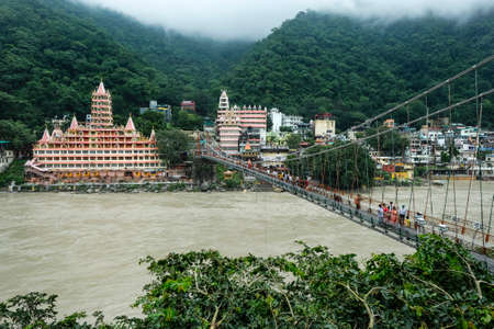 Rishikesh, India - July 2021: People passing by the Lakshman Jhula Bridge next to the Swarg Niwas Temple in Rishikesh on July 20, 2021 in Uttarakhand, India.