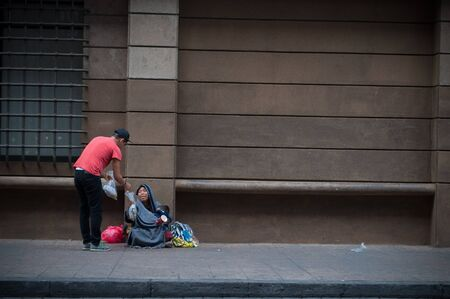 路上で人に食べ物を届ける若者。