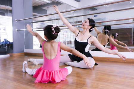 Ballet teacher and little student practicing postions sitting on the floor Stockfoto