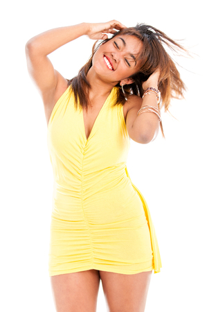 Beautiful woman in a yellow dress dancing and looking very happy - isolated