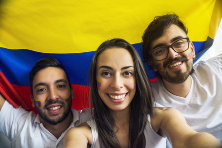 Young colombian soccer fans taking a selfie with a flag in their backs