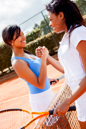 Female tennis players handshaking at the end of a match