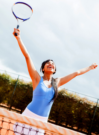 Female tennis player winning with arms up