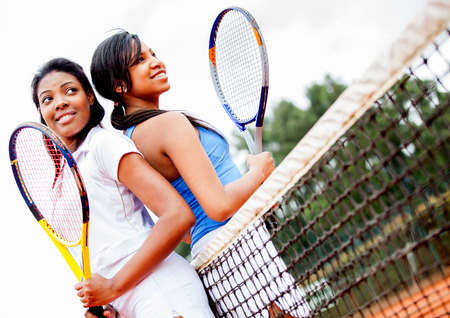 Female tennis players holding rackets at the court