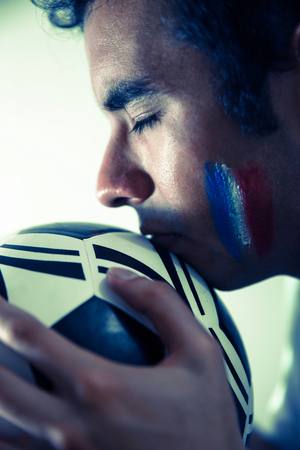 Young soccer fan with closed eyes holding a soccer ball