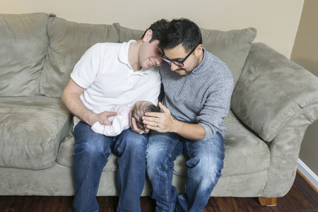 Young gay couple with adopted baby