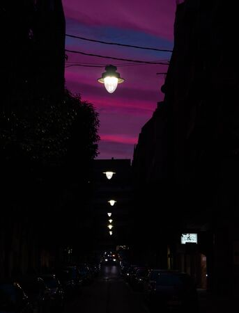night street with nas hanging lights. Bluish sky and soft magenta color with a car approaching with the lights on
