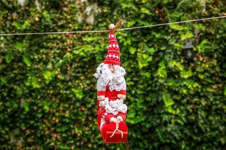 Little Santa Claus hanging on a rope, in a yard
