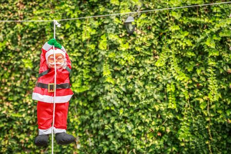 A santa claus doll hanging on a rope in a courtyard