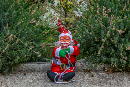 An endearing Santa Claus sitting in the middle of the garden of a village house