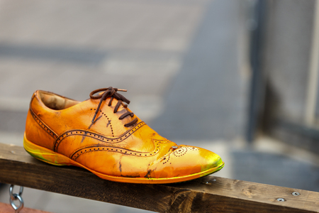 An old and lonely shoe on top of a piece of wood on the street Stock Photo
