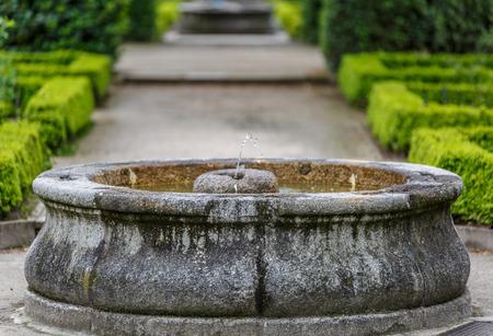jet stream: fuente de piedra en medio de un hermoso jardín botánico Foto de archivo
