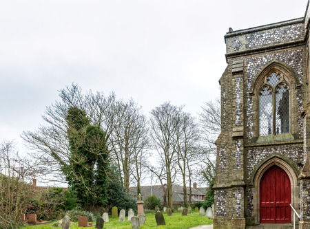 county side: Side of a church in the middle of a cemetery in England, in Norfolk County Stock Photo
